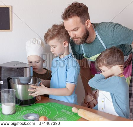 Happy Father With Children Cooks On Paternity Leave In The Kitchen