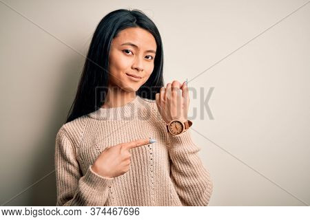 Young beautiful chinese woman wearing casual sweater over isolated white background In hurry pointing to watch time, impatience, looking at the camera with relaxed expression