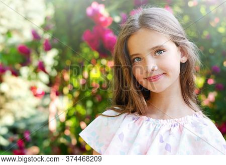 Portrait Of Adorable Smiling Little Girl Child In Summer Day. Happy Preteen In The Park Outdoors
