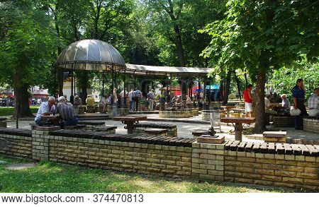Ukraine, Kiev 05/07/2012 . Elderly Men Play Chess In A City Square In The Shade Of Chestnuts And Arb