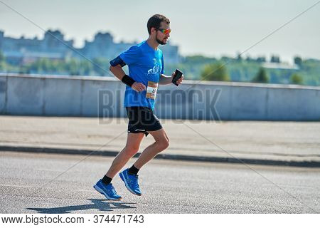 Voronezh, Russia - 24.08.2019 - Young Man Runs Along Road. Runners Marathon And Championship Competi