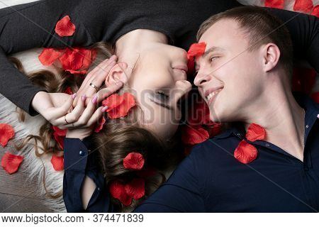 Loving Couple. Man And Woman In Rose Petals. Beautiful Young Husband And Wife.close-up Man And Woman
