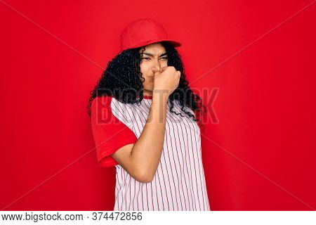 Young african american curly sportswoman wearing baseball cap and striped t-shirt smelling something stinky and disgusting, intolerable smell, holding breath with fingers on nose. Bad smell