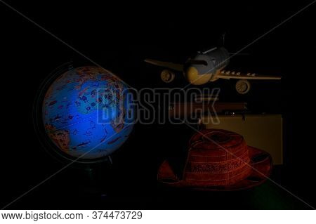 Backlit Globe Lamp, Airplane Suitcases And Hat In The Dark, Adventure Concept