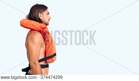 Young handsome man wearing nautical lifejacket looking to side, relax profile pose with natural face with confident smile.