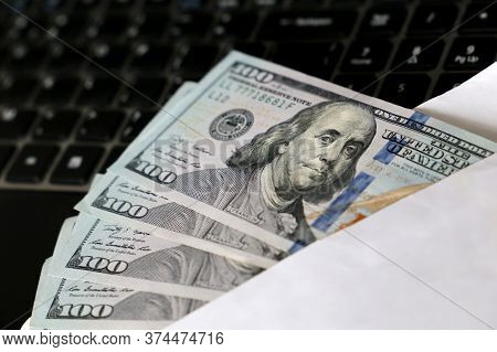 Us Dollars In White Envelope On Laptop Keyboard Background. Income, Wages Or Bribe Concept