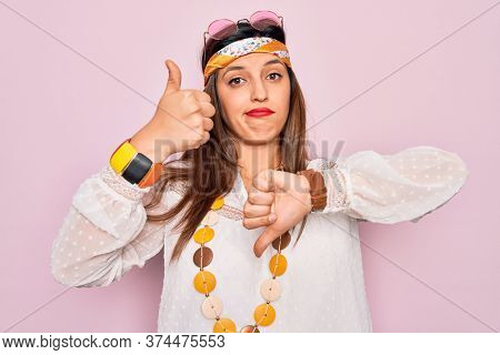 Young hispanic hippie woman wearing fashion boho style and sunglasses over pink background Doing thumbs up and down, disagreement and agreement expression. Crazy conflict