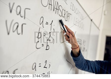 Cropped Shot Of A Male Teacher Pointing At Text On Whiteboard While Giving Javascript Lesson Online.