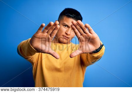 Young handsome latin man wearing yellow casual sweater over isolated blue background doing frame using hands palms and fingers, camera perspective