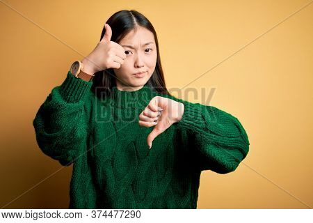 Young beautiful asian woman wearing green winter sweater over yellow isolated background Doing thumbs up and down, disagreement and agreement expression. Crazy conflict