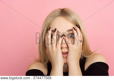 Shocked Hiding Face. Portrait Of Young Caucasian Woman With Bright Emotions On Coral Pink Studio Bac