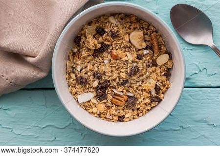 Granola In Bowl With Raisins,dried Banana,  Nuts - Top View Breakfast Muesli On Rustic Blue Table Ba