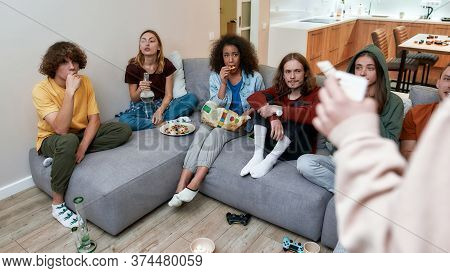 Young Multicultural People Eating Snacks, Playing Video Games After Smoking Marijuana From A Bong Wh