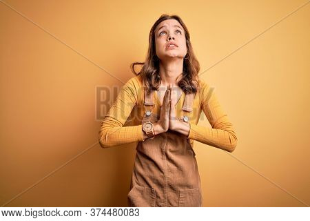 Young beautiful blonde girl wearing overall standing over yellow isolated background begging and praying with hands together with hope expression on face very emotional and worried. Begging.