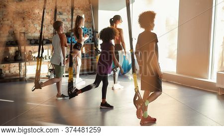 Portrait Of Teenage Kids Training Using Fitness Straps In Gym With Female Trainer. Sport, Healthy Li