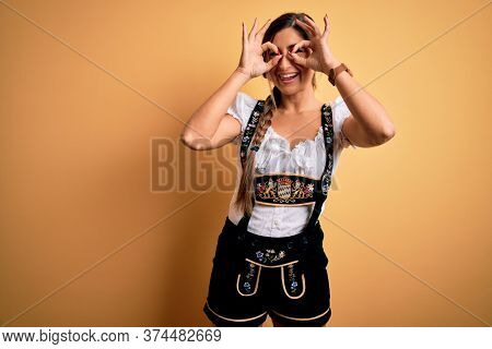 Young beautiful brunette german woman celebrating Octoberfest wearing traditional dress doing ok gesture like binoculars sticking tongue out, eyes looking through fingers. Crazy expression.
