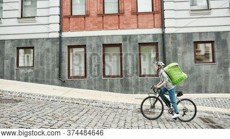 Young Delivery Woman In Helmet With Thermo Bag Or Backpack Riding A Bike Along The City, Delivering