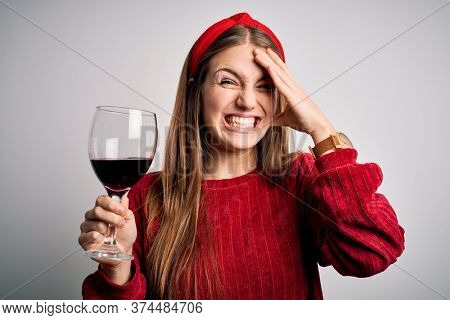 Young beautiful redhead woman drinking glass of red wine over isolated white background stressed with hand on head, shocked with shame and surprise face, angry and frustrated. Fear and upset.