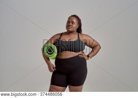 Plump, Plus Size African American Woman In Sportswear Holding Green Yoga Mat For Fitness, Posing In