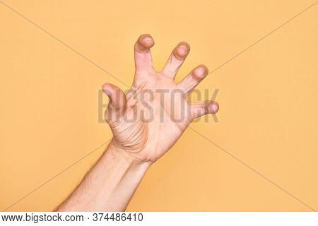 Hand of caucasian young man showing fingers over isolated yellow background grasping aggressive and scary with fingers, violence and frustration