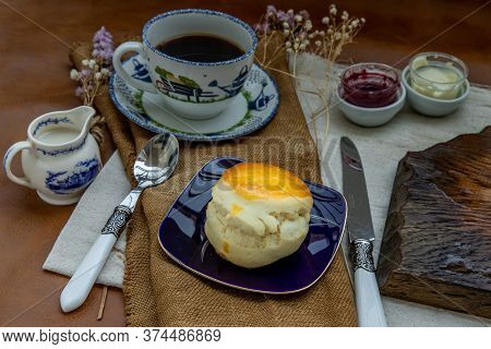 Scones With Mascarpone Cheese And Raspberry Jam Served With Black Coffee With Milk On Sack Cloth For