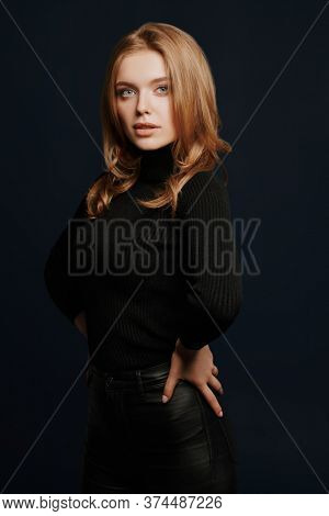 Beauty portrait. Gorgeous young woman with blonde hair and beautiful blue eyes posing in black turtleneck on a dark blue background.