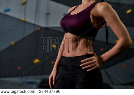 Cropped Shot Of Active Young Woman In Sportswear Showing Her Sportive Body, Abs, Standing Against Ar