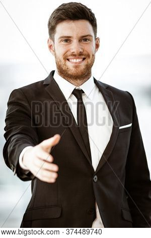 Business concept. Successful young businessman at work. Manager standing in office happy reaches out for a handshake. Man smiling in suit indoors on glass window background.
