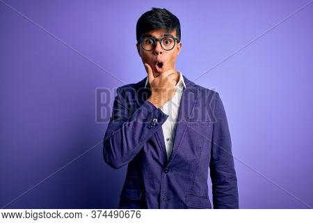 Young handsome business man wearing jacket and glasses over isolated purple background Looking fascinated with disbelief, surprise and amazed expression with hands on chin