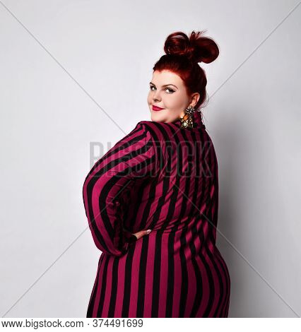 Fat Ginger Woman With Bun Hairstyle, In Black And Purple Striped Dress And Golden Earrings. She Has