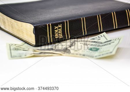 A Holy Christian Bible With A Twenty Dollar Bill Isolated On A White Background.