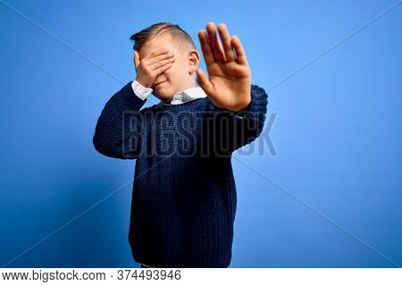 Young little caucasian kid with blue eyes wearing winter sweater over blue background covering eyes with hands and doing stop gesture with sad and fear expression. Embarrassed and negative concept.