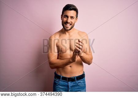 Young handsome strong man with beard shirtless standing over isolated pink background clapping and applauding happy and joyful, smiling proud hands together