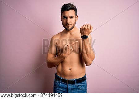 Young handsome strong man with beard shirtless standing over isolated pink background In hurry pointing to watch time, impatience, looking at the camera with relaxed expression
