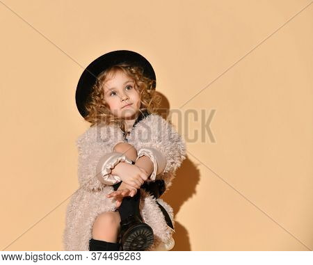 Blonde Curly Little Lady In Pink Faux Fur Coat, Black Hat And Boots. She Hugged Her Crossed Legs Whi