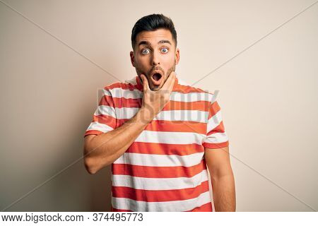 Young handsome man wearing casual striped t-shirt standing over isolated white background Looking fascinated with disbelief, surprise and amazed expression with hands on chin