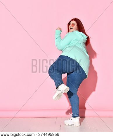 Pleasant Fatty Woman With Long Foxy Hair Posing On One Leg Looking Over Her Shoulder In A Figure Of