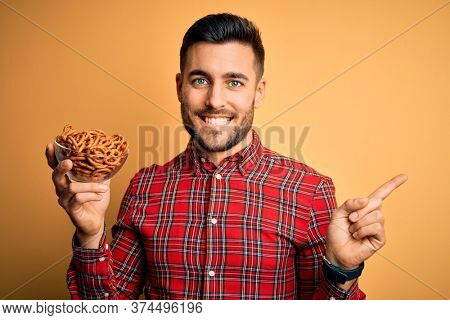 Young handsome man holding bowl with baked German pretzels over yellow background very happy pointing with hand and finger to the side