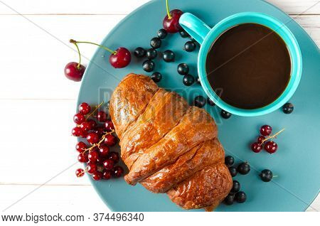 Homemade Pastries. A Ruddy Croissant With Berries Lies On A Bright Plate Next To A Cup Of Coffee