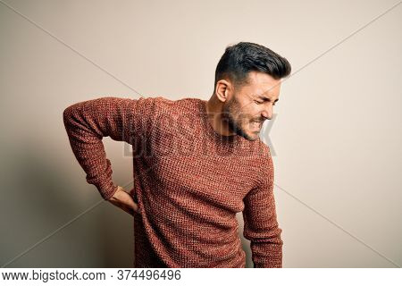 Young handsome man wearing casual sweater standing over isolated white background Suffering of backache, touching back with hand, muscular pain