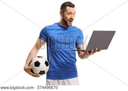 Excited soccer player holding a ball and a looking at a laptop computer isolated on white background