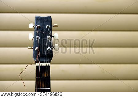 Guitar Neck And Head In Bad Condition With Broken Strings In Front Of House Wall Front View Close Up