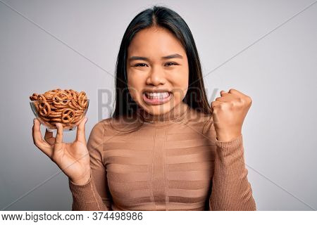 Young asian girl holding bowl with baked german pretzels over isolated white background screaming proud and celebrating victory and success very excited, cheering emotion