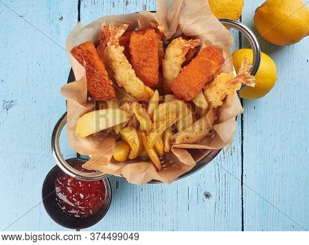 Fried Fish Fingers, Tempura Prawns And Potato Wedges In A Colander, With Lemons And Sriracha Sauce,