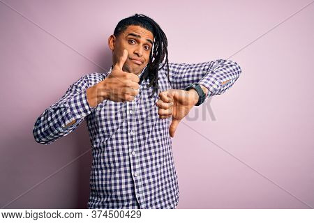 Young handsome african american afro man with dreadlocks wearing casual shirt Doing thumbs up and down, disagreement and agreement expression. Crazy conflict