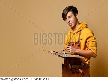 Painter Guy In Yellow Hoodie And Jumpsuit Standing And Painting On Easel Over Yellow Background. Sty