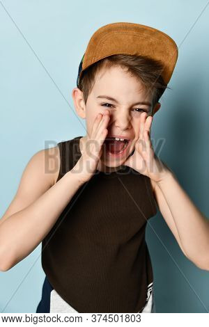 Sly Little Boy In Black Sleeveless Shirt And Cap Shouting Loudly Holding Hands Near Opened Mouth. Ch