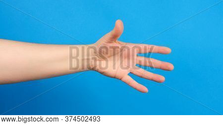 Outstretched Hand Of Man, Open Hand, Part Of The Body On A Blue Background, Close Up