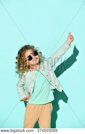 Cute Little Curly Girl With Black Non-transparent Glasses On Face Stands Raising One Hand And Pointi