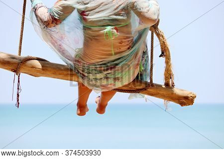 Woman Swinging On A Wooden Swing Against The Blue Sea. Beach Holidays On A Tropical Resort, Concept